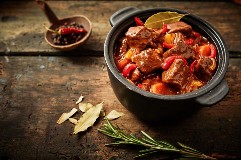 Pot of hungarian goulash on rustic wood background with chili peppers and laurel and copy space.jpg